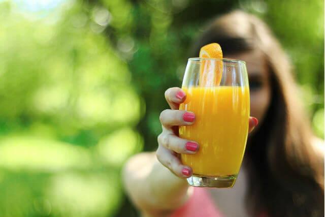 前に突き出されたオレンジジュース