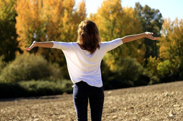 空に向かって両手を広げる女性